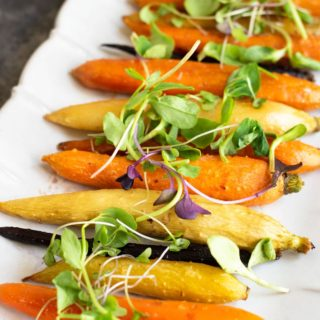 a platter with whole maple roasted carrots, topped with sprouts