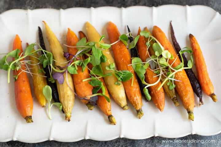 a horizontal picture of a platter of maple carrots