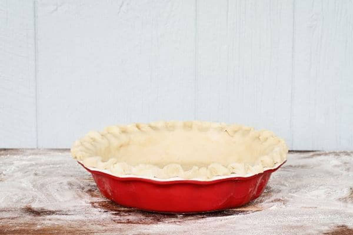 a pie crust in a red pie pan ready to bake