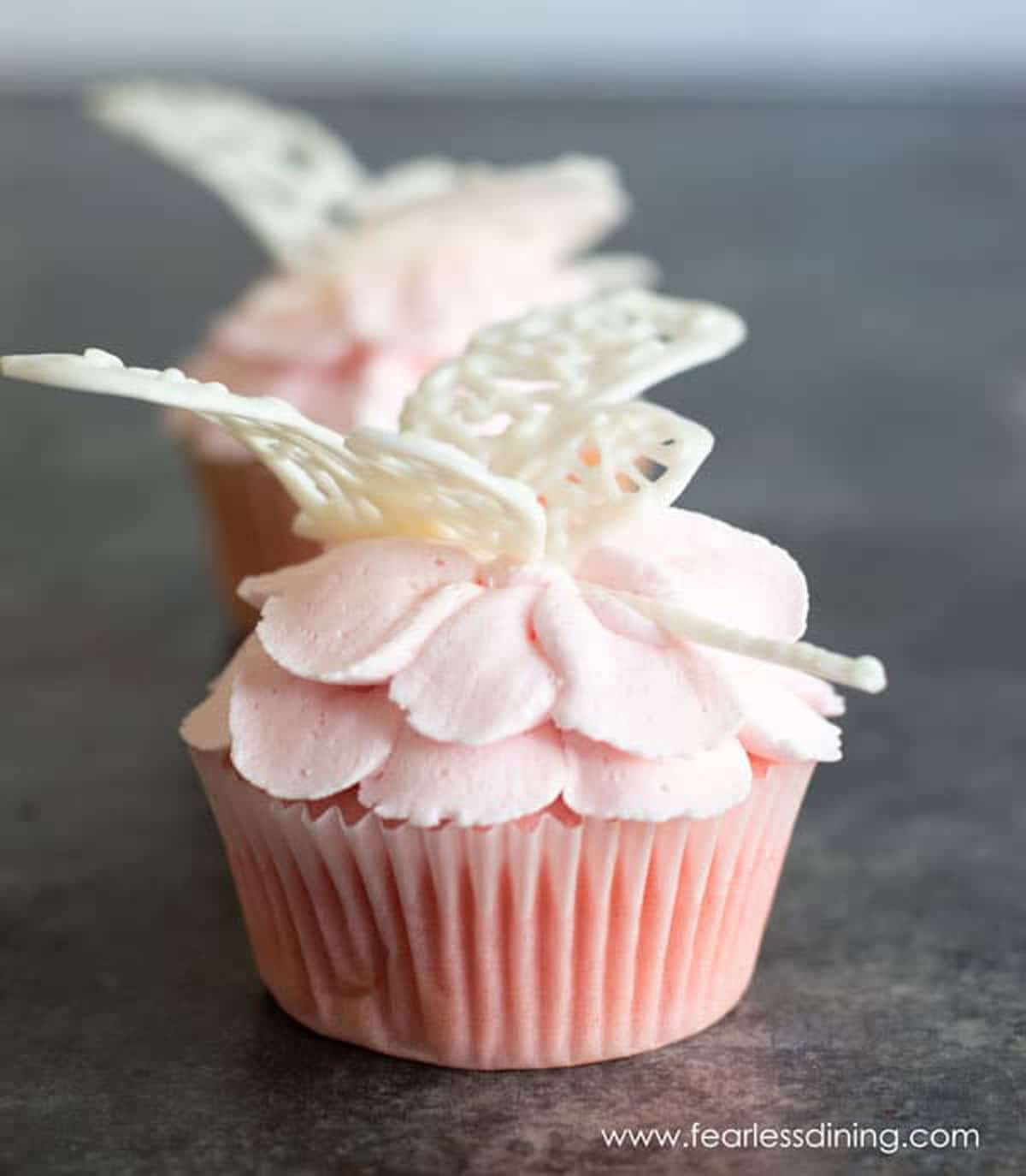 pink flower cupcakes topped with white chocolate dragon flies