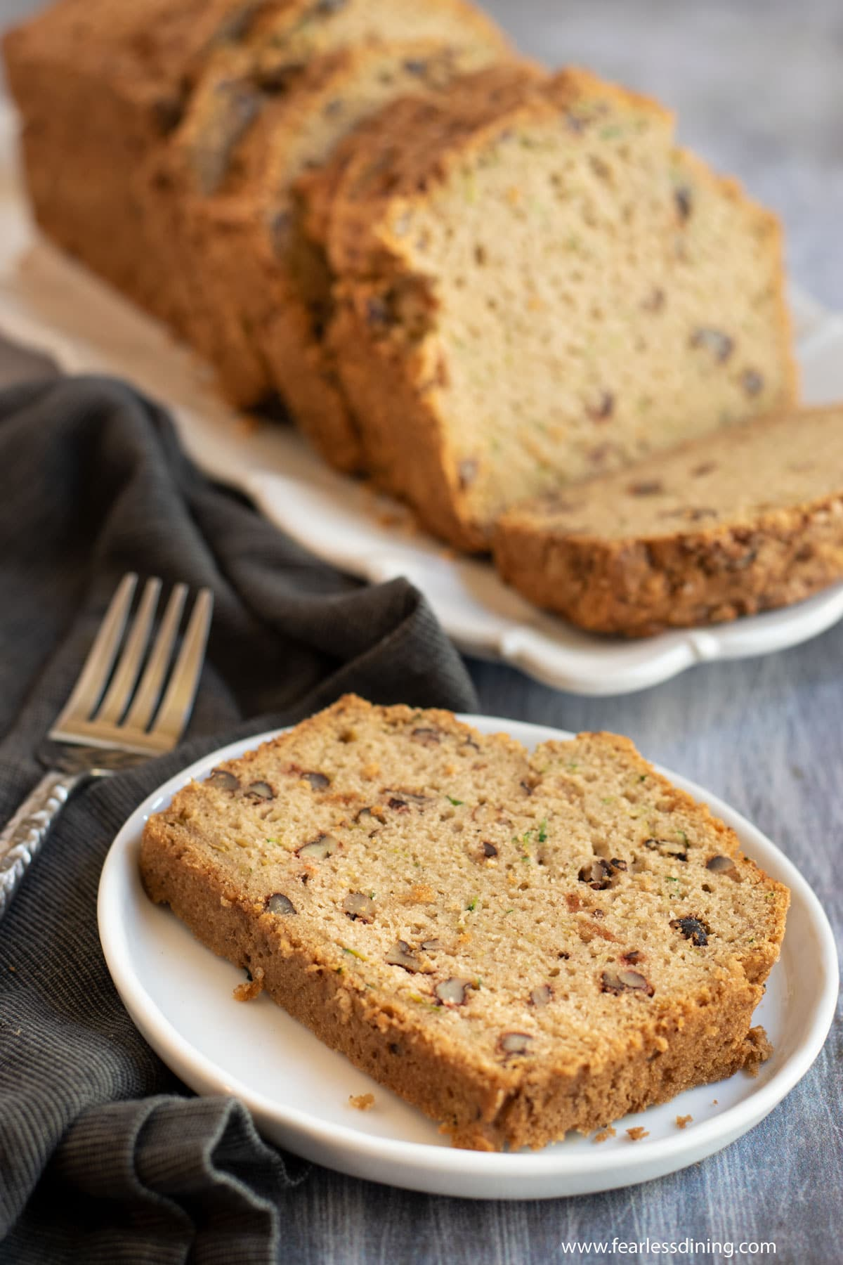 a slice of zucchini bread on a plate next to the loaf