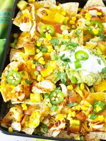a close up of a tray of nachos topped with sour cream