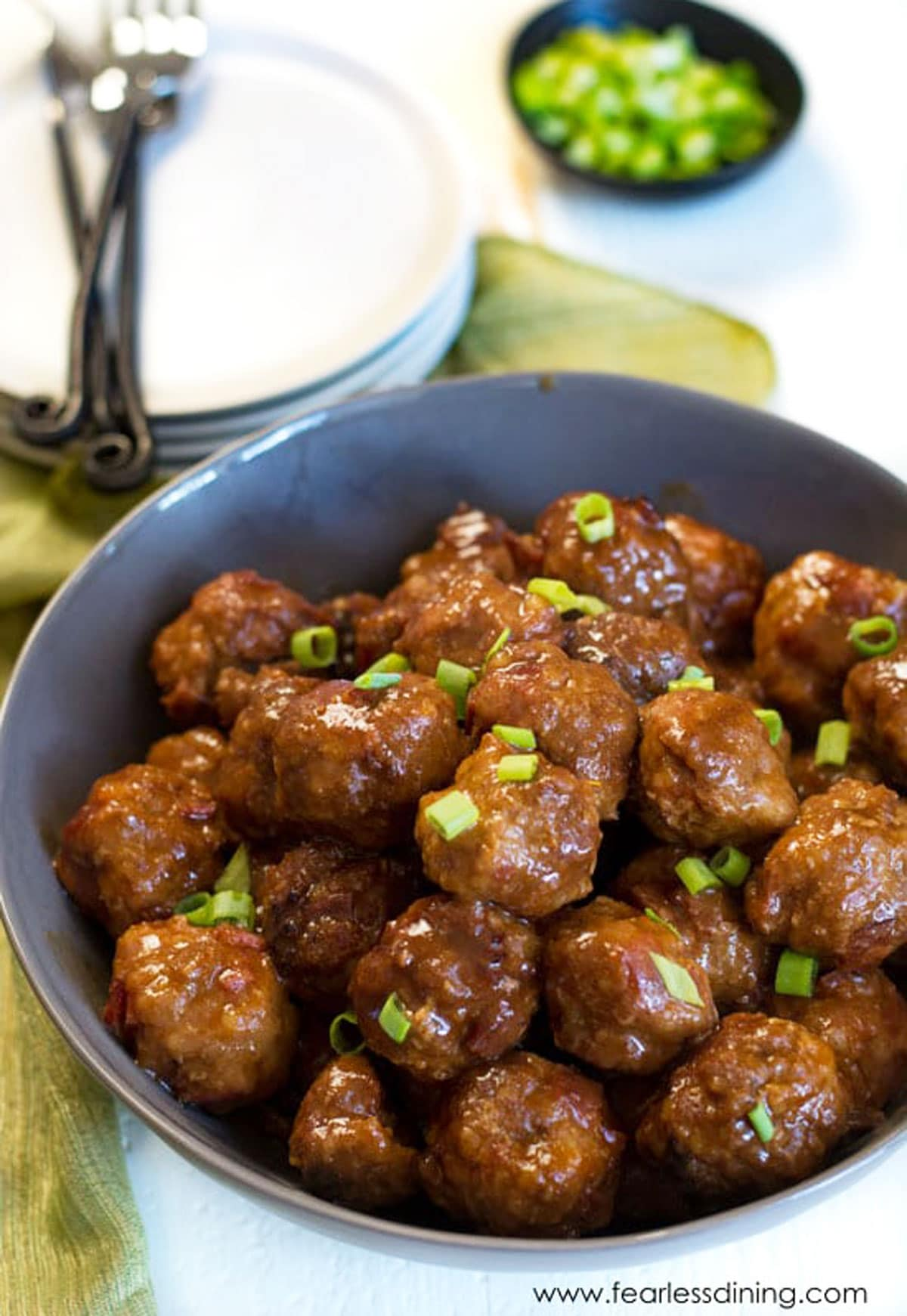 a large grey bowl full of meatballs. They are garnished with scallions