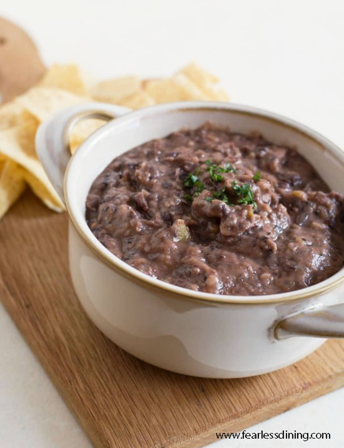 a bowl full of black bean dip on a wooden serving tray