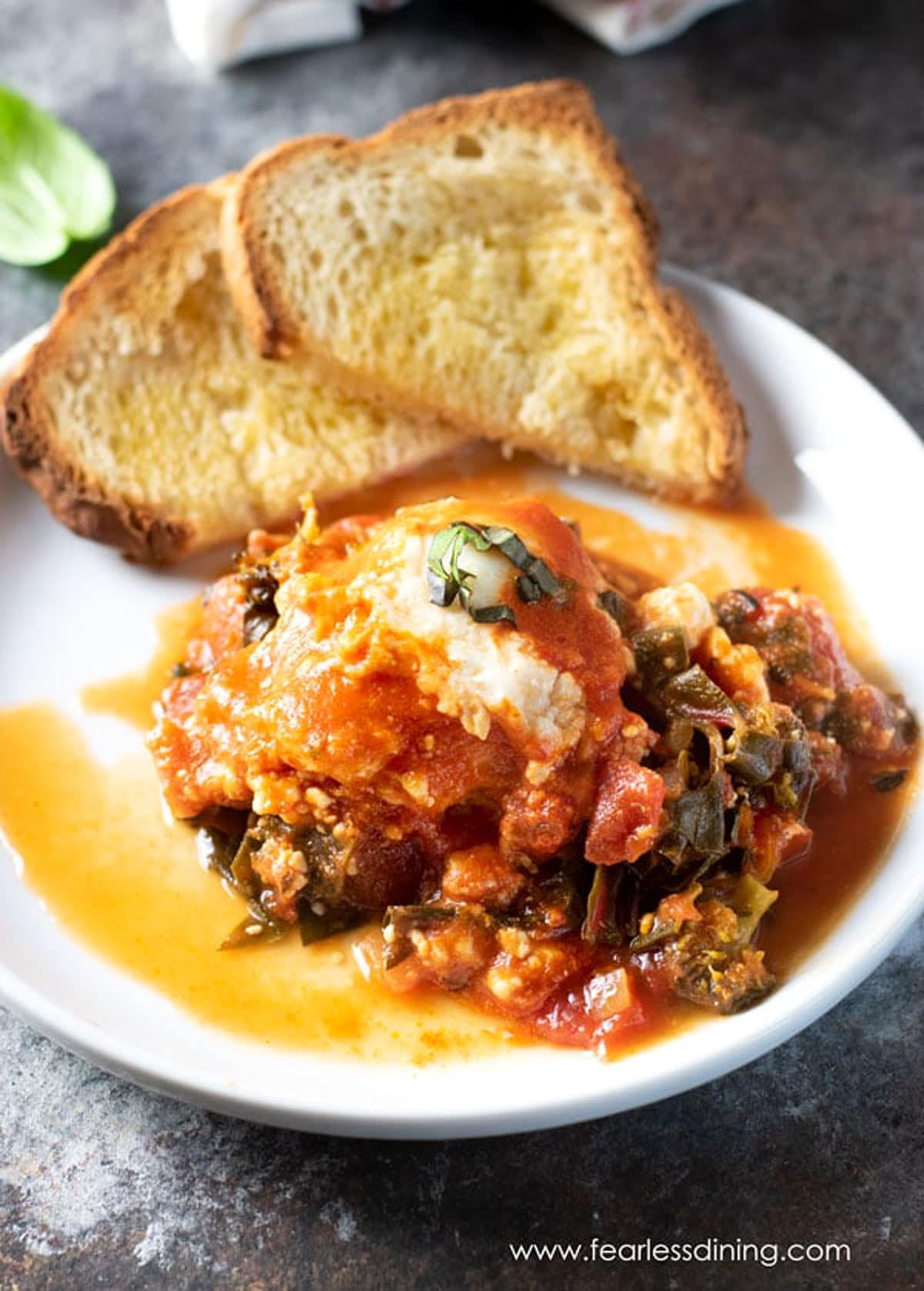 a plate filled with shakshuka and toast