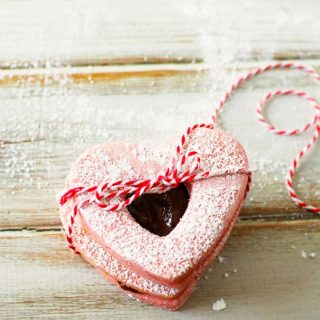 heart shaped pink linzer cookies tied by a string