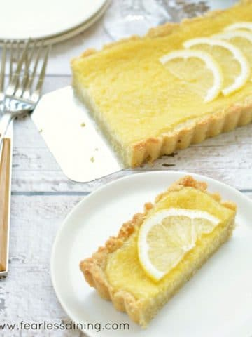 a slice of lemon tart on a white plate next to the whole tart