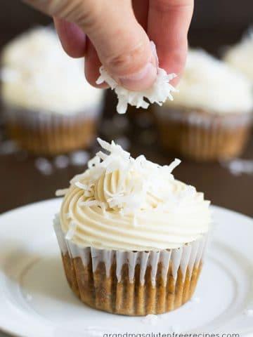 sprinkling coconut over a cupcake
