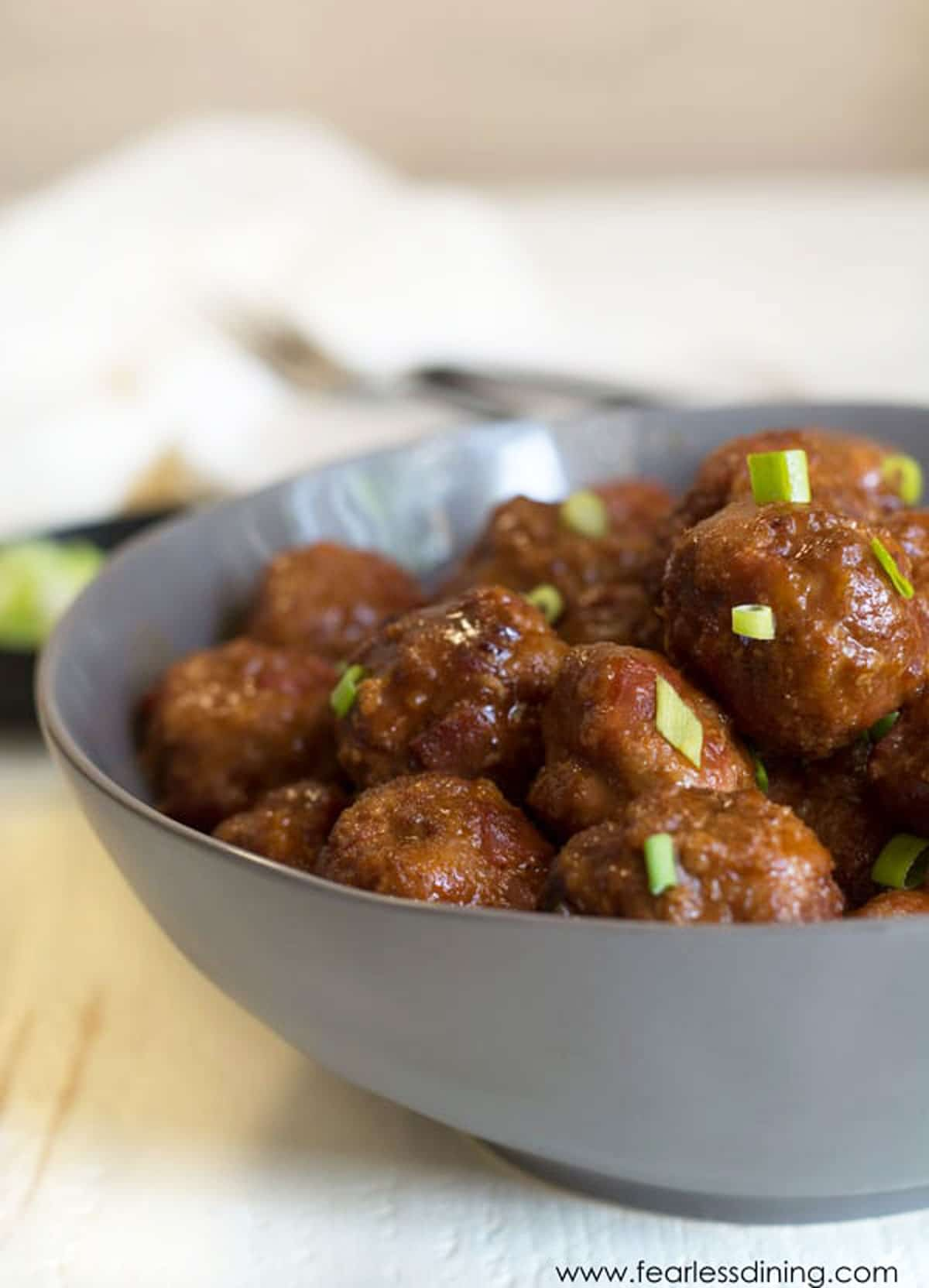 a grey bowl filled with BBQ meatballs
