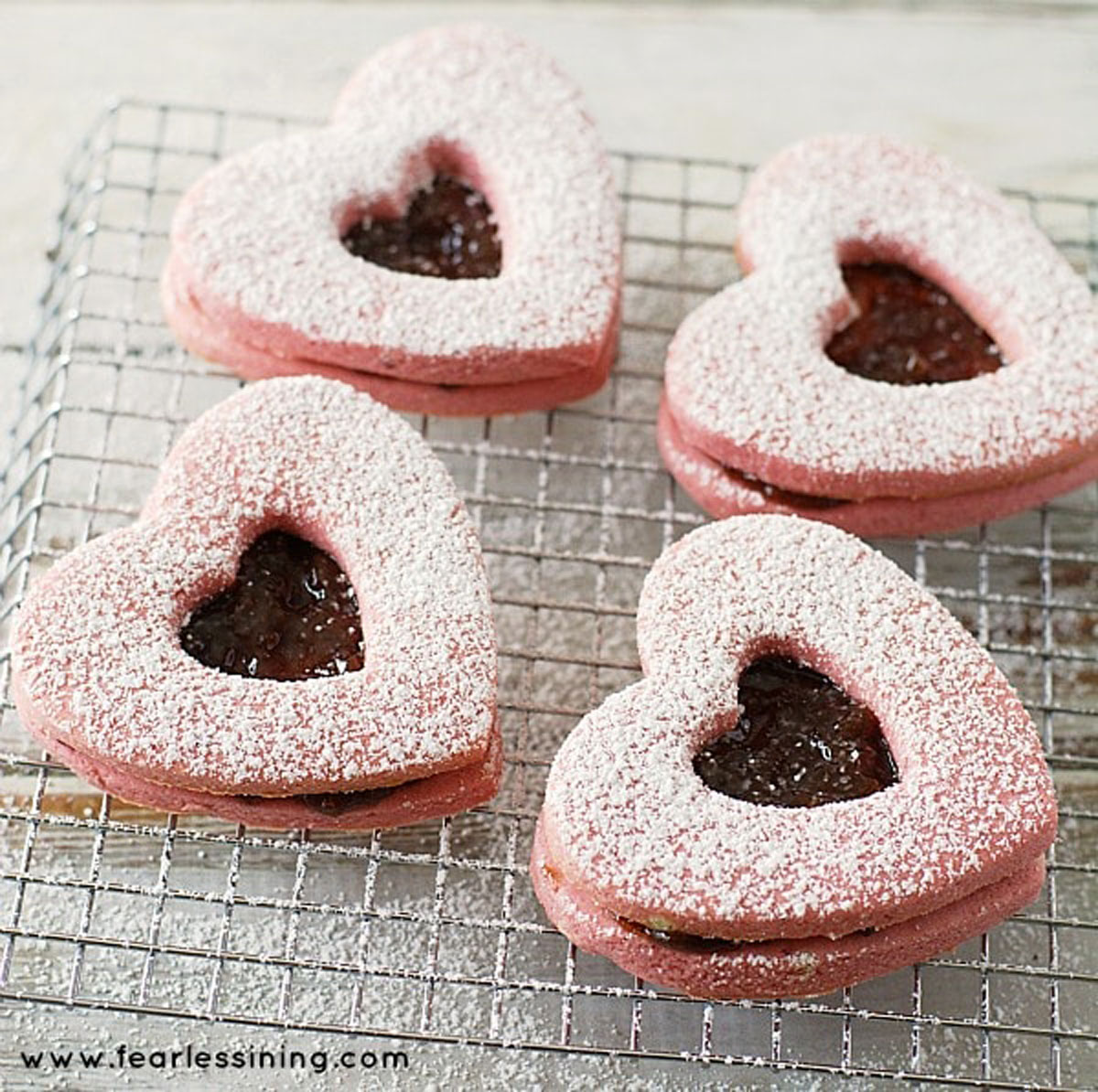powdered sugared dusted linzer cookies on a rack