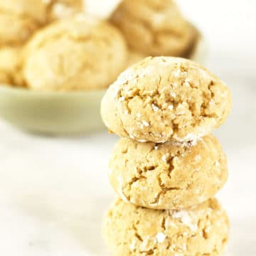 a stack of honey cookies next to a bowl of cookies