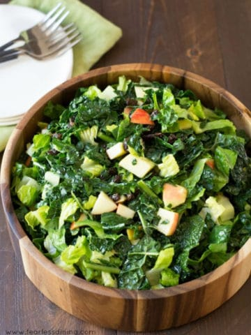 close up of the kale and apple salad in a wooden bowl