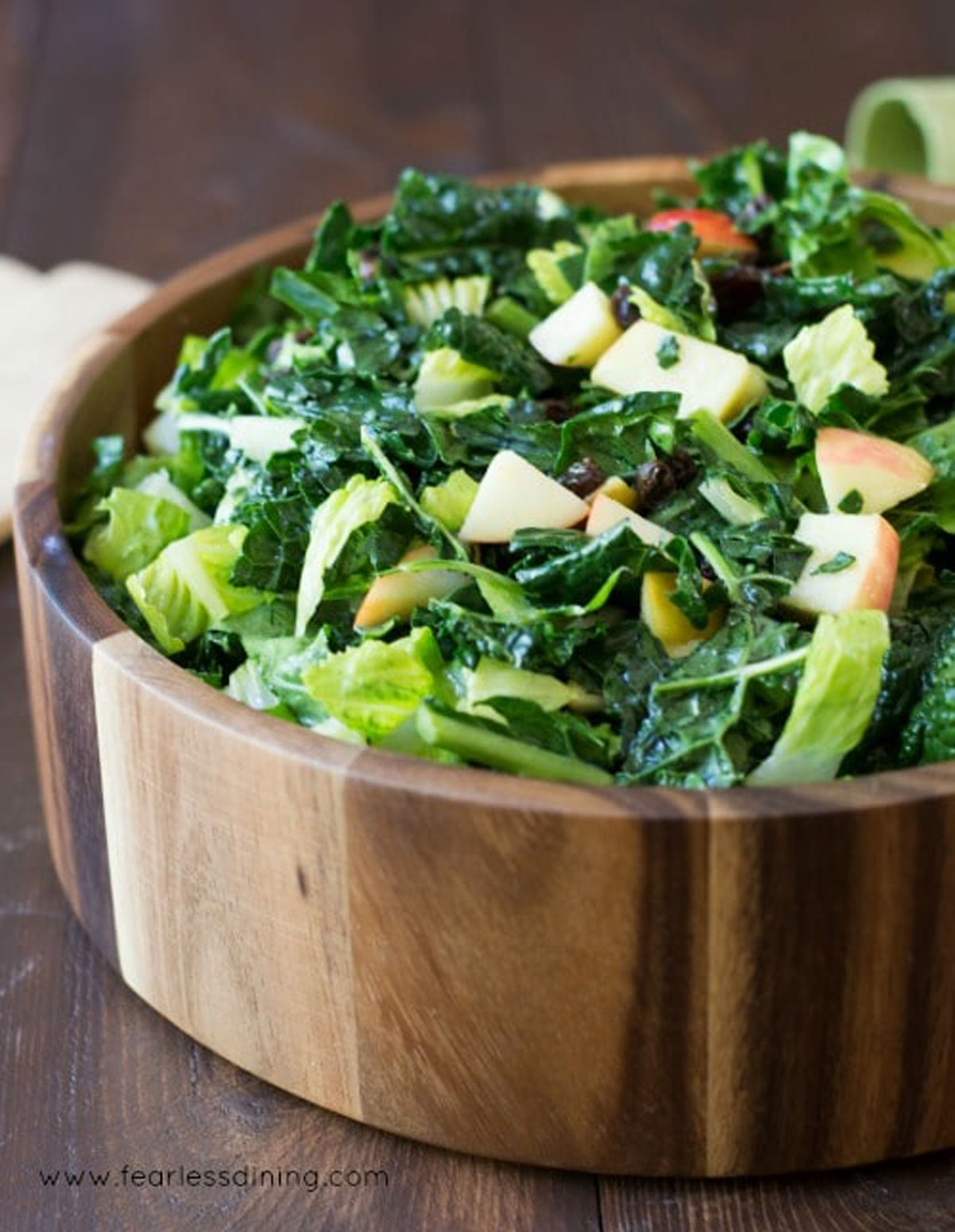 side view of a big wooden bowl filled with kale salad