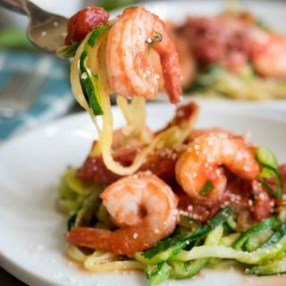 a fork full of zucchini noodles and a cooked shrimp