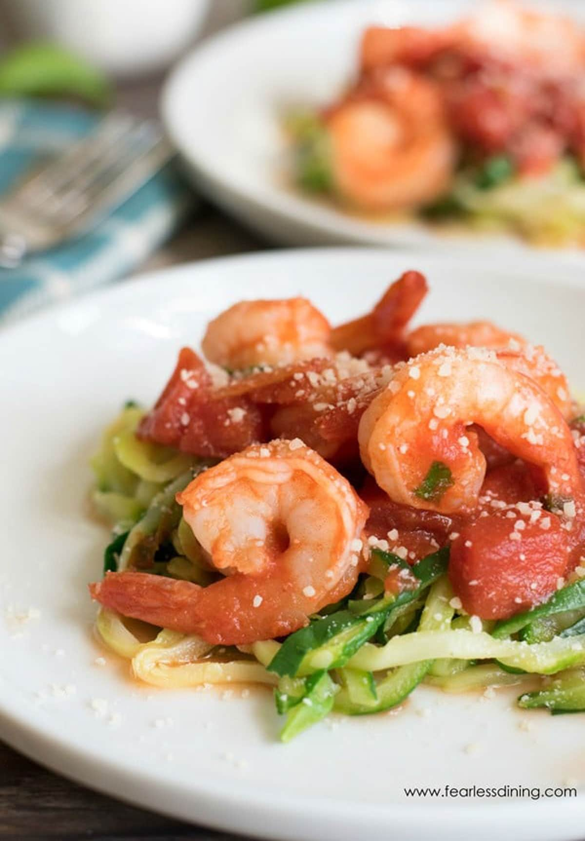 two plates of shrimp diavolo over zucchini noodles.