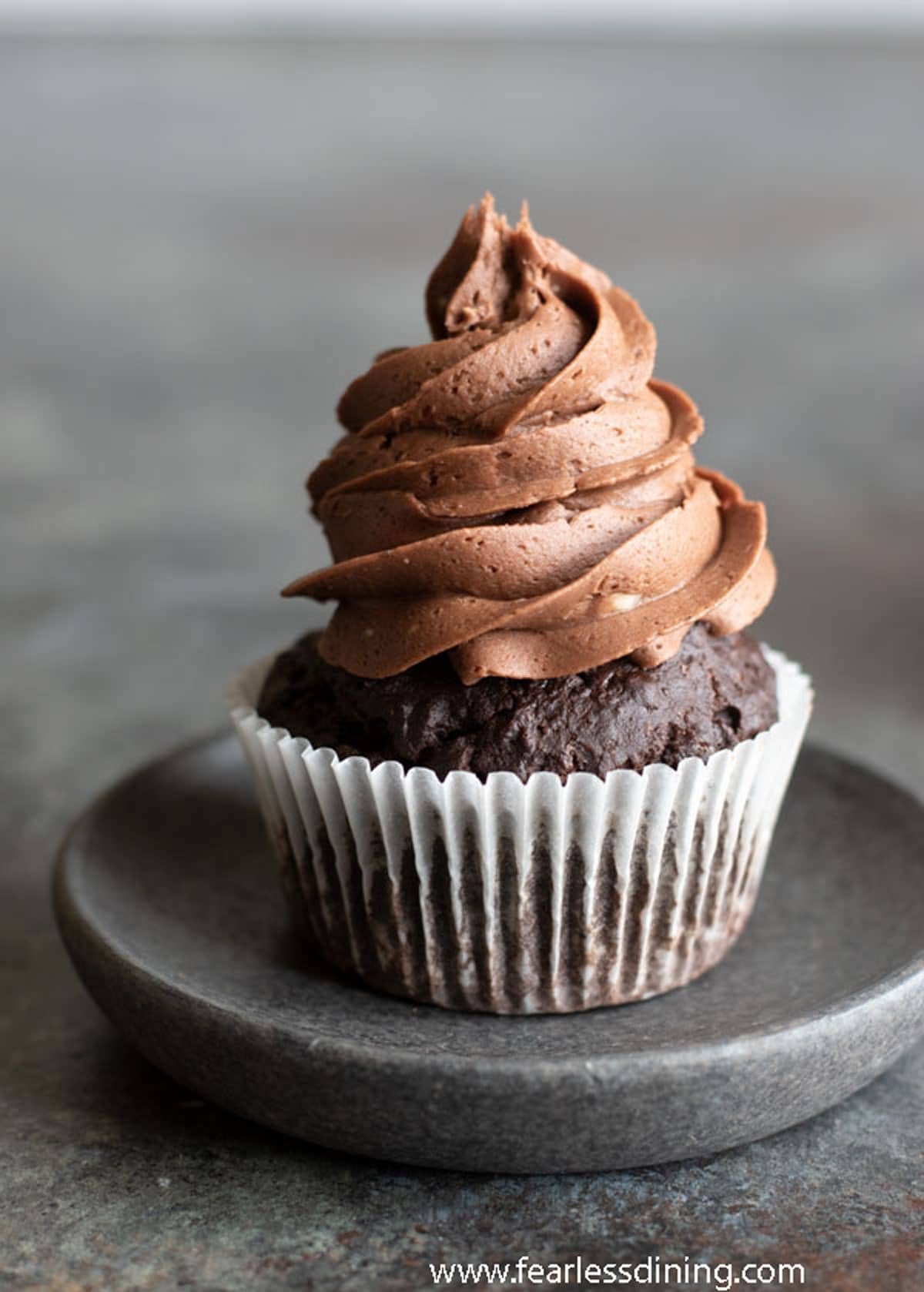 a single chocolate cupcake on a charcoal grey plate