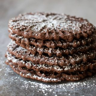 a stack of chocolate pizzelle cookies