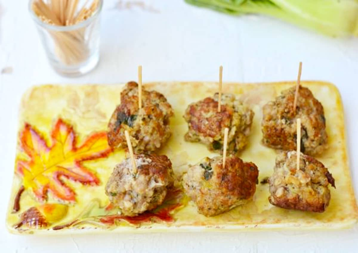 a platter filled with meatballs. Each meatball has a toothpick in it.