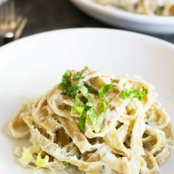 a plate of fettuccine alfredo topped with fresh basil