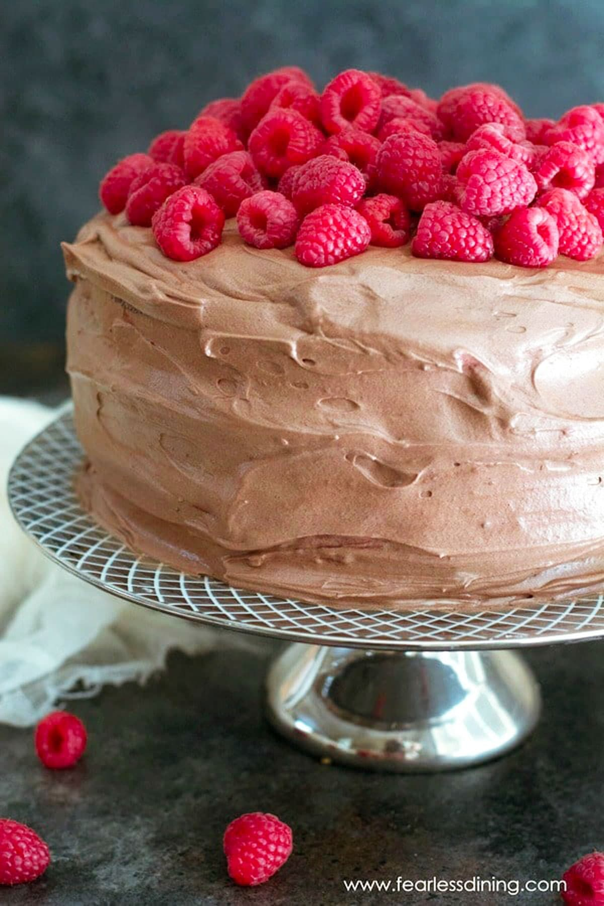 a frosted chocolate cake topped with fresh raspberries