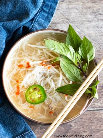 a top view of a big bowl of chicken pho. Chopsticks are resting on the lip of the bowl