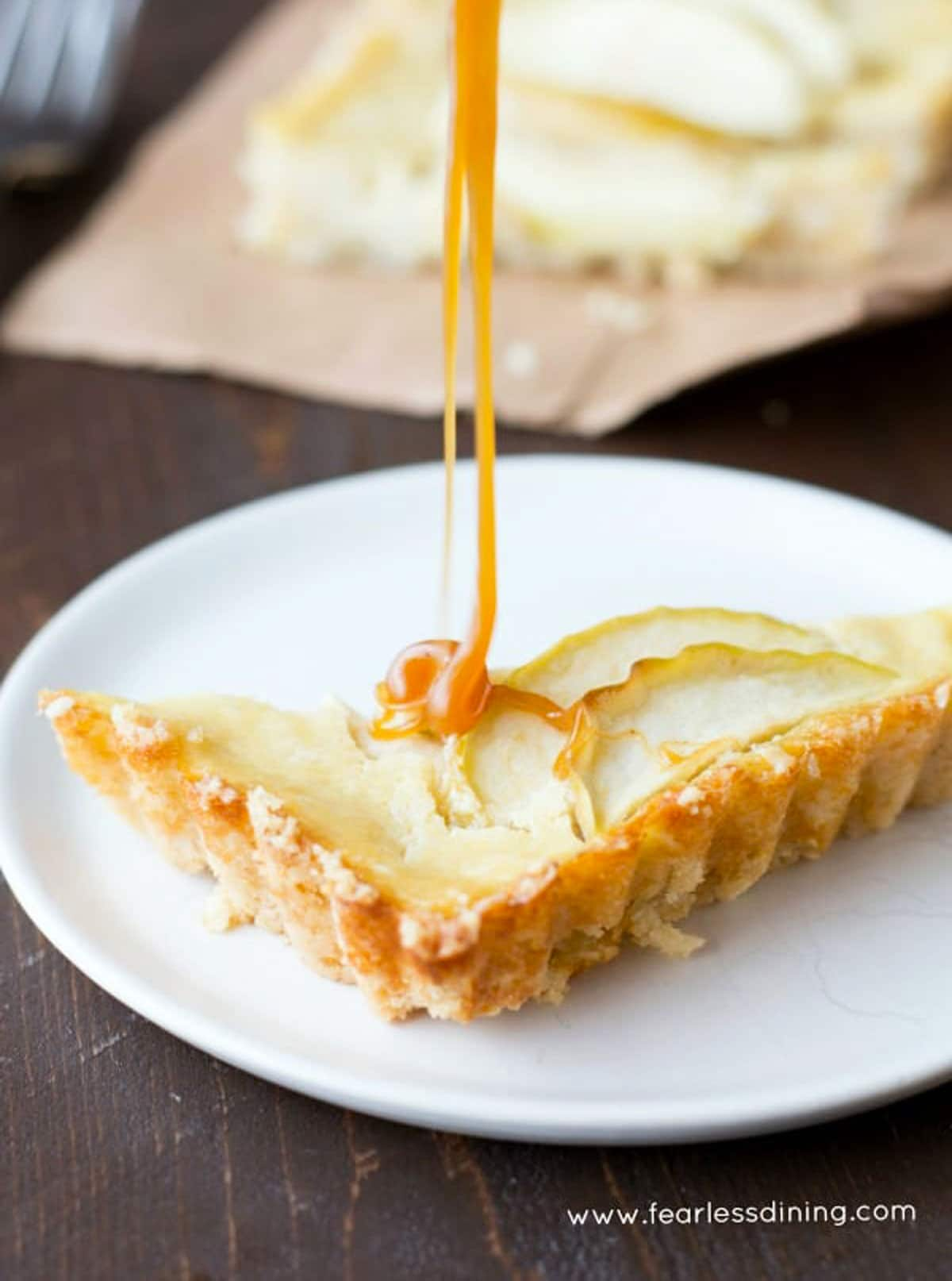 drizzling caramel over a slice of apple tart