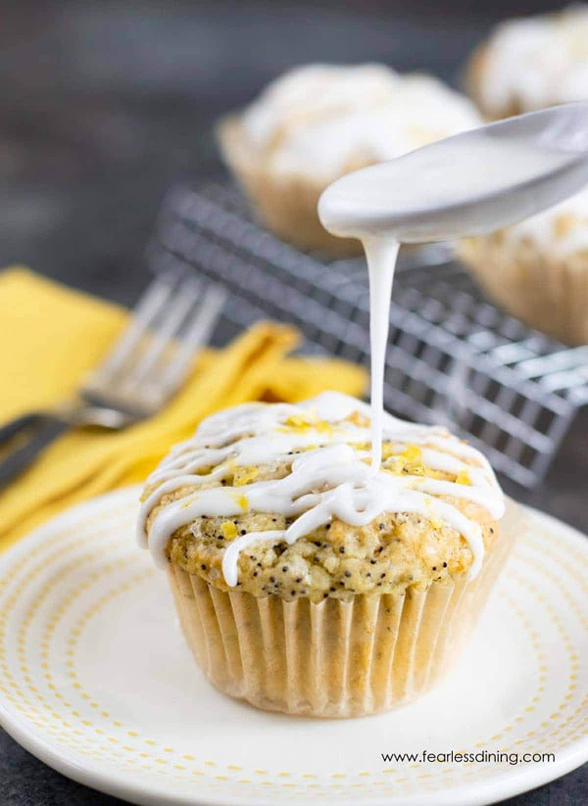a spoon drizzling icing over a lemon poppy seed muffin