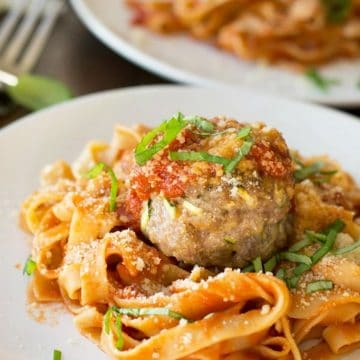 a plate with gluten free pasta with a large meatball on top