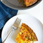 the top view of a slice of quiche on a plate next to the whole quiche