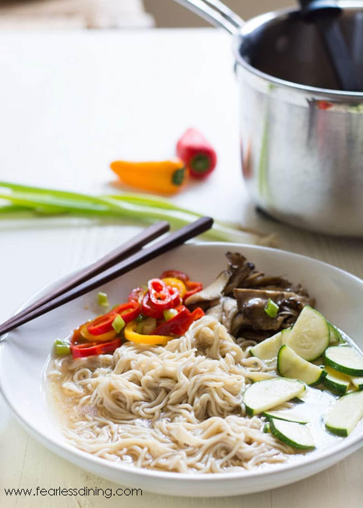 a bowl of gluten free ramen next to the pot of soup