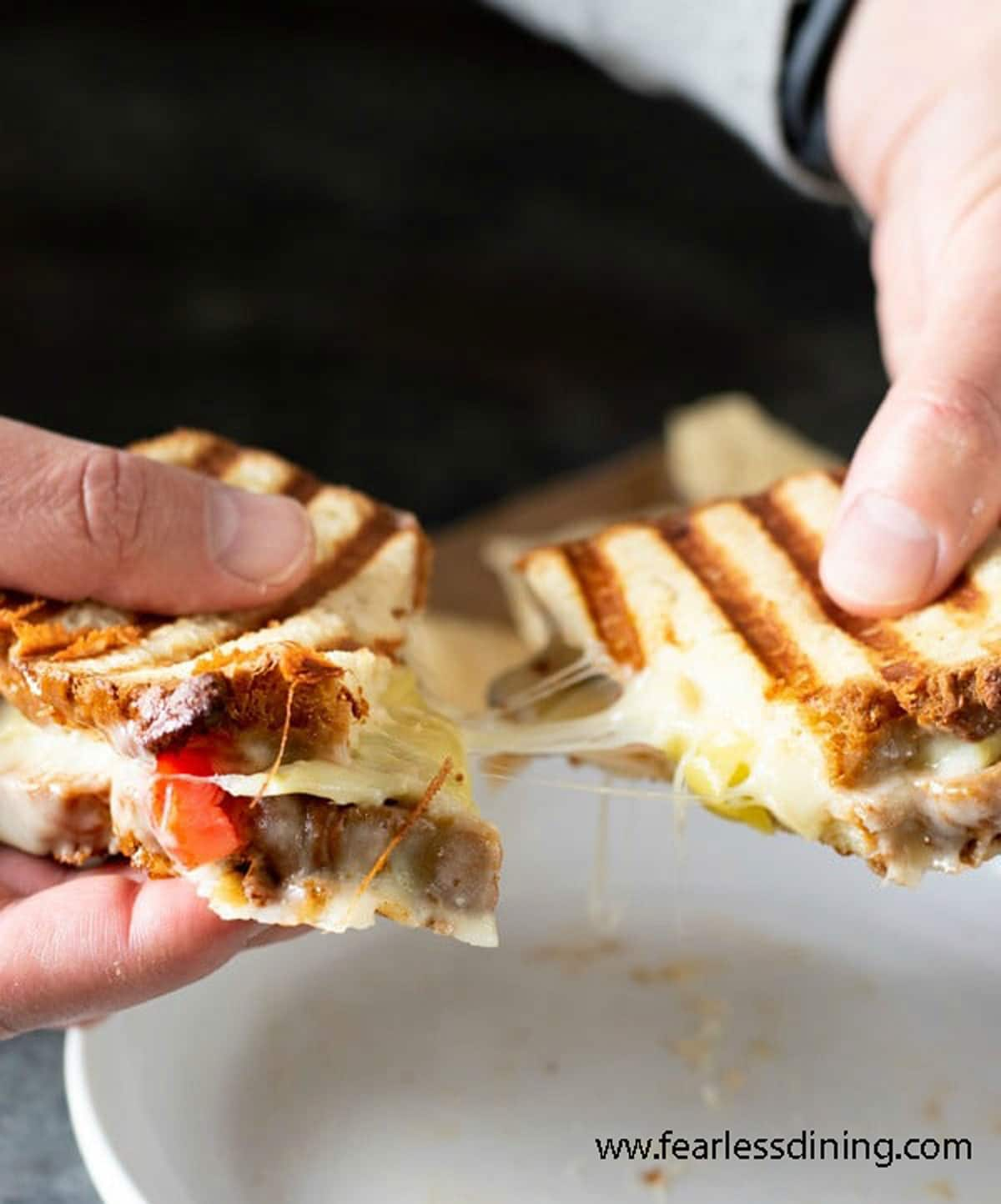 holding a panini with stretching melted cheese