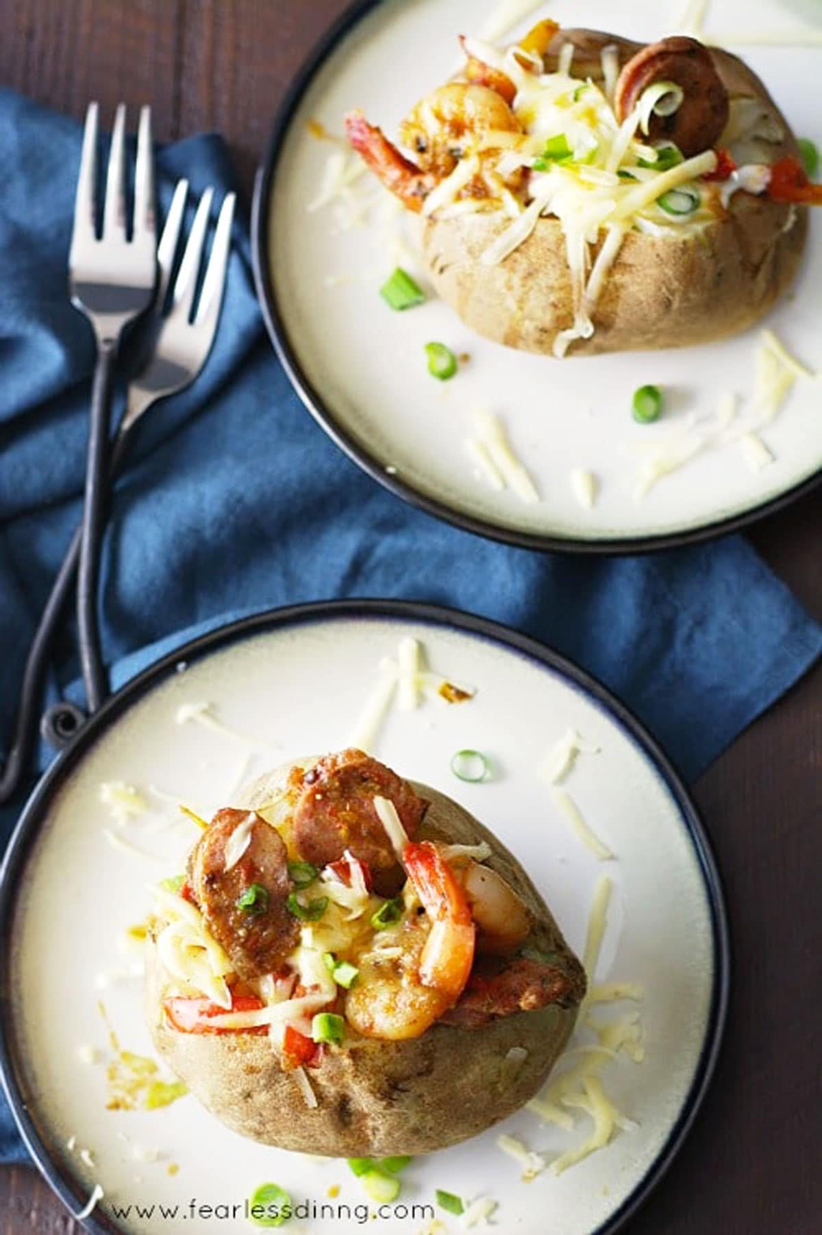 the top view of two jambalaya stuffed baked potatoes on plates