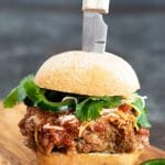 a meatloaf burger on a cutting board with a knife stabbing into it
