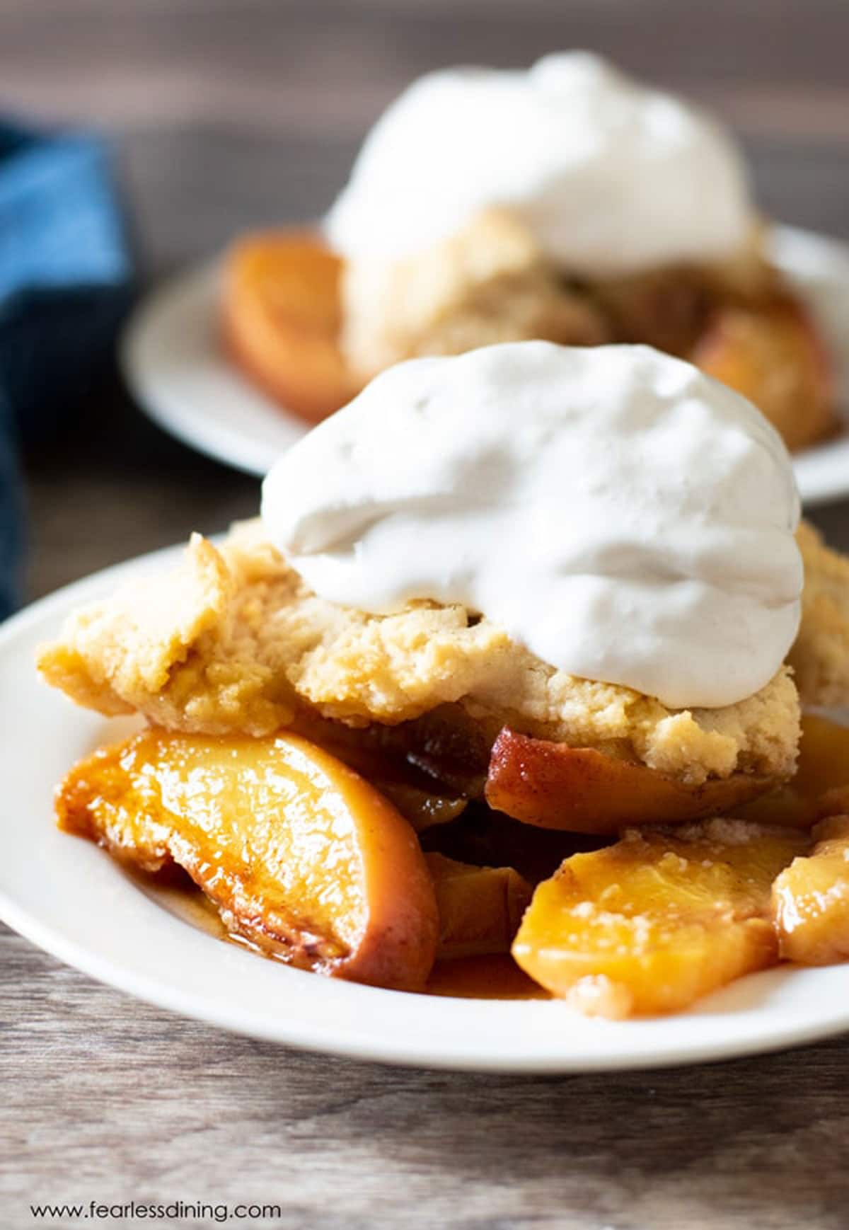 a serving of peach cobbler topped with whipped cream