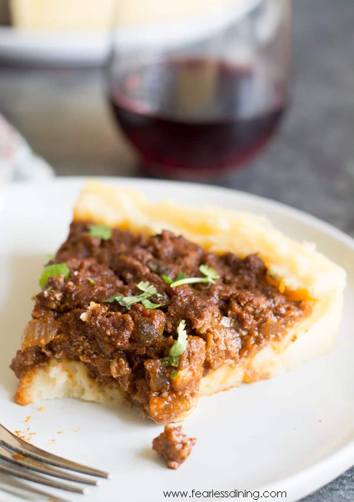 a slice of sloppy joe pie with  piece cut out with a fork