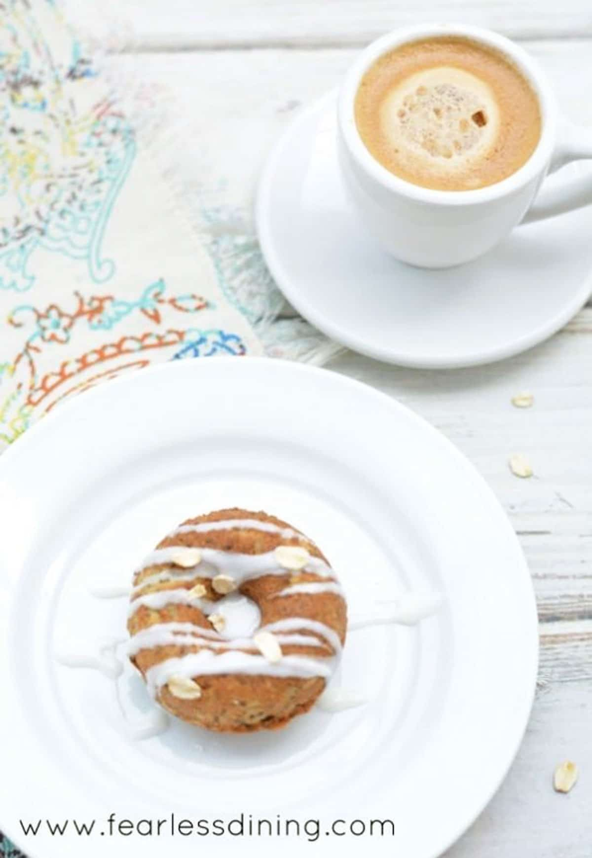 a donut on a white plate next to an espresso