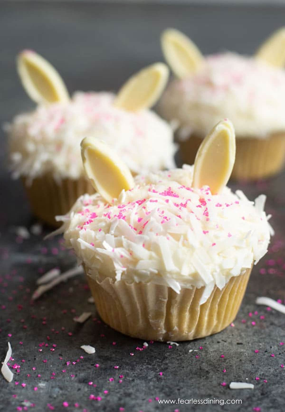 coconut cupcakes decorated with white chocolate bunny ears for Easter