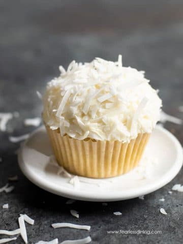 a single coconut cupcake on a small white plate