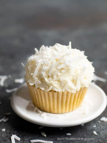 a gluten free coconut cupcake on a small white plate