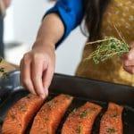 a hand dropping fresh herbs on raw salmon