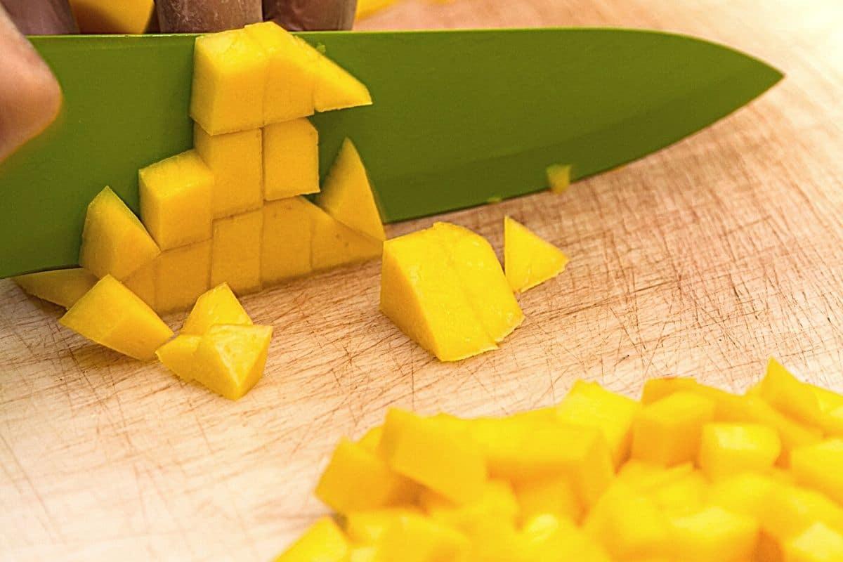 cutting mango on a wooden cutting board