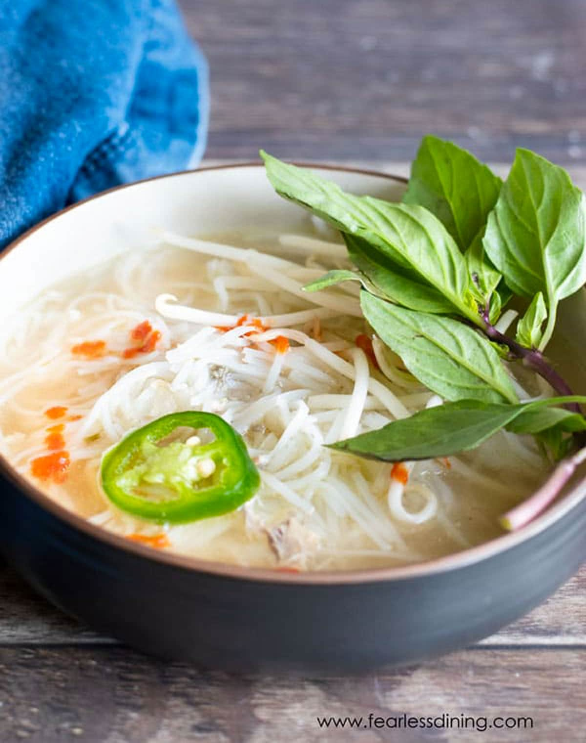 a bowl of pho topped with basil and jalapeño