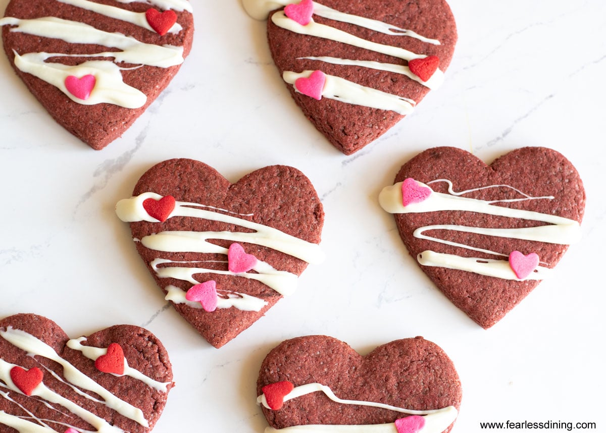 decorated red velvet heart shaped cookies on a tray