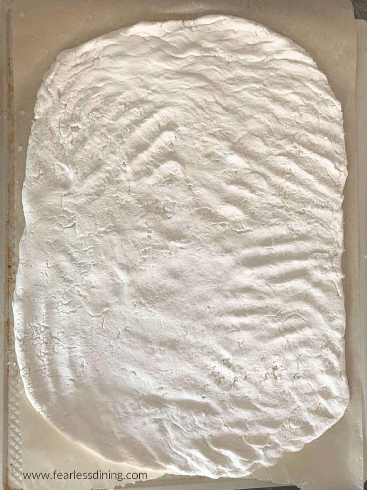 a pizza crust on a baking sheet