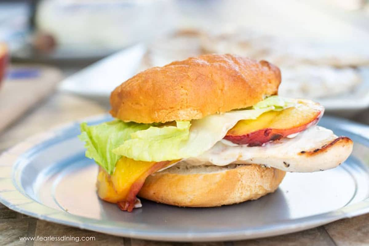 a grilled chicken burger on a paper plate