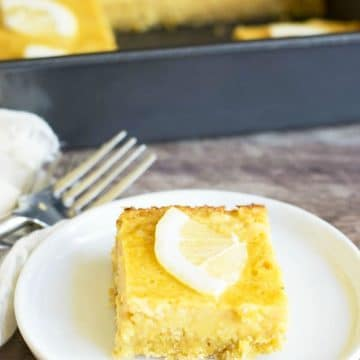 a lemon bar on a small white plate in front of the pan