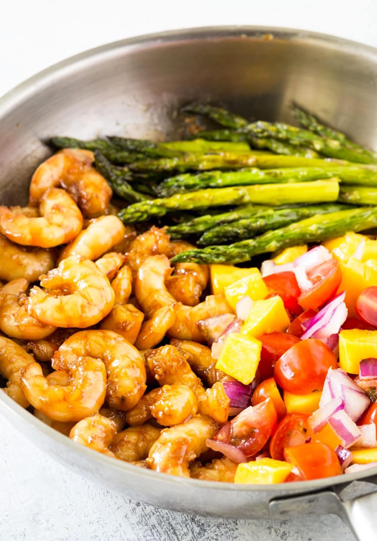 a pan filled with honey garlic shrimp, asparagus, and mango salsa