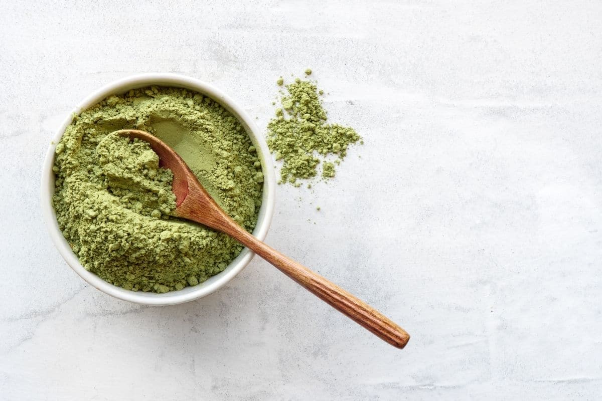 matcha powder in a white bowl with a wooden spoon