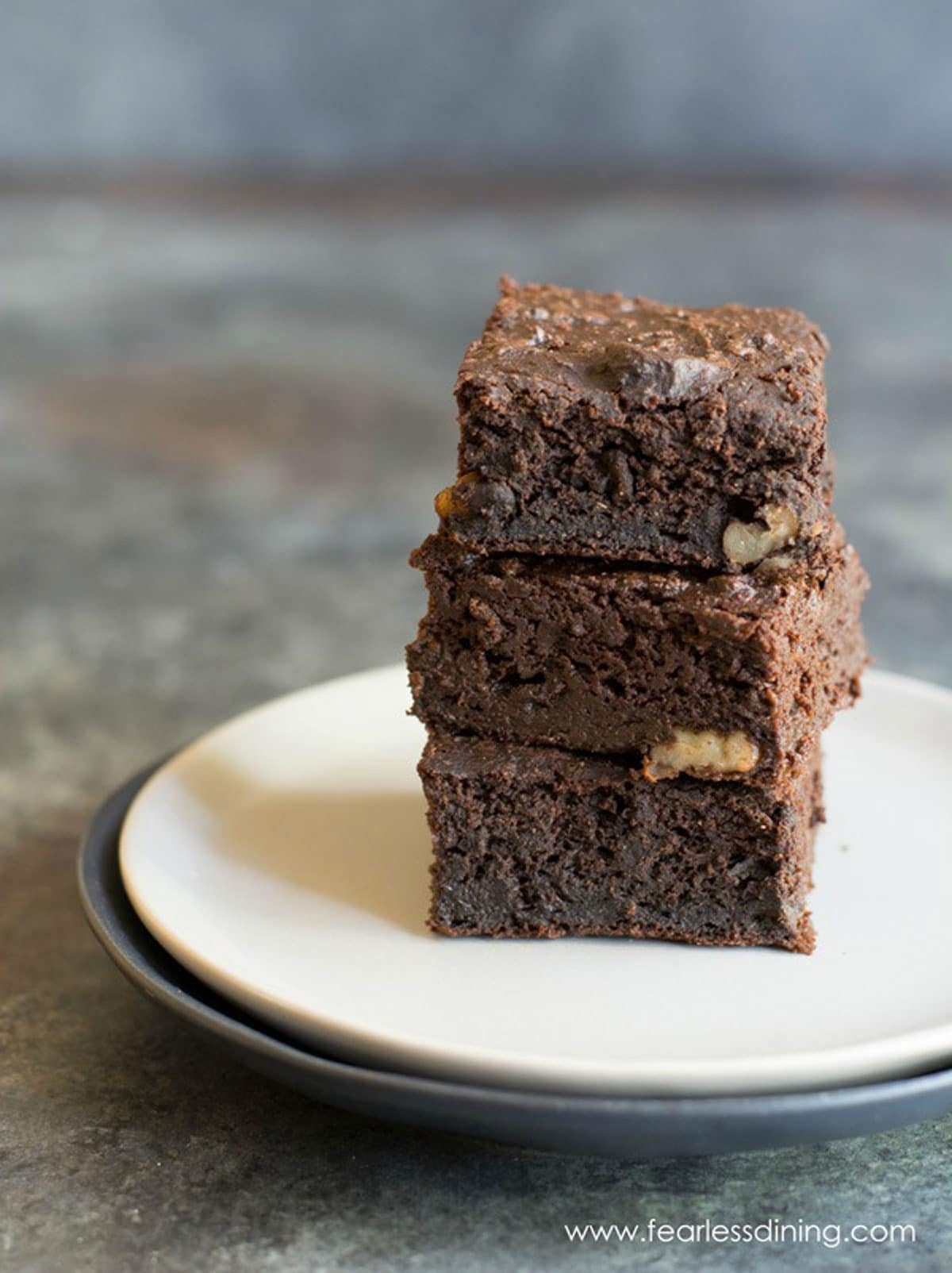 a stack of three brownies on a plate