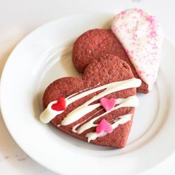 two decorated heart shaped red velvet cookies on a small white plate